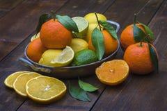 金属碗用在竹桌上的柑橘水果 免版税图库摄影