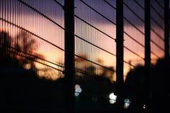 金属篱芭和天空在日落 免版税库存图片
