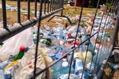金属篱芭扔的塑料瓶 被丢掉的使用的空的宠物瓶和在草离开在一个露天党以后 库存图片