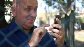金属篱芭文本的保护的商人使用手机和微笑 影视素材