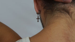 金属耳环细节有垂悬在一个人的耳朵的十字架的 库存图片