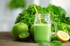 金属螺盖玻璃瓶与蔬菜和水果的绿色健康汁液 免版税库存图片