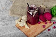 金属螺盖玻璃瓶与黑秸杆的甜菜根汁在木背景 一块姜、甜菜和荷兰芹在切板 免版税库存图片