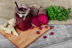 金属螺盖玻璃瓶与黑秸杆的甜菜根汁在木背景 一块姜、甜菜和荷兰芹在切板 库存图片