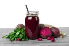 金属螺盖玻璃瓶的特写镜头甜菜根圆滑的人,明亮的紫罗兰色甜菜,在白色隔绝的芬芳姜立方体  免版税图库摄影