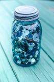 金属螺盖玻璃瓶充满按钮 免版税图库摄影