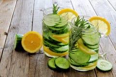 金属螺盖玻璃瓶戒毒所浇灌用柠檬,在木头的黄瓜 免版税图库摄影