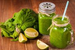 金属螺盖玻璃瓶杯子充满绿色菠菜和无头甘蓝健康圆滑的人打旋了秸杆 免版税库存图片