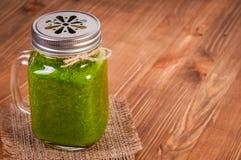 金属螺盖玻璃瓶杯子充满绿色菠菜和无头甘蓝健康圆滑的人打旋了秸杆 图库摄影