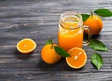 金属螺盖玻璃瓶杯子用橙汁 库存照片