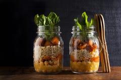 金属螺盖玻璃瓶用热的沙拉:鸡豆, arrots,奎奴亚藜,烤了Pu 免版税库存图片