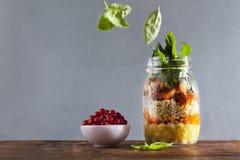 金属螺盖玻璃瓶用热的沙拉:鸡豆, arrots,奎奴亚藜,烤了Pu 免版税库存照片