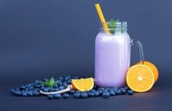 金属螺盖玻璃瓶从成熟蓝莓的圆滑的人,一半在黑暗的背景的橙色和绿色薄菏 滋补维生素 库存照片