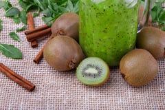 金属螺盖玻璃瓶从猕猴桃、肉桂条和叶子的绿色圆滑的人在一张白色桌布 饮料的猕猴桃 免版税库存照片