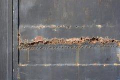 金属表面上的深灰破裂的绘画 免版税库存图片