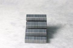 金属钉书针投入了对被塑造的楼梯在白色织品地板 免版税库存图片