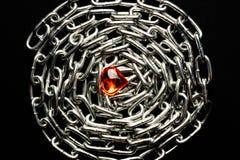 金属链子在黑背景排行了在玻璃心脏的中心 免版税库存图片