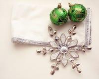 金属雪剥落和两个绿色圣诞节球在白色和银餐巾 免版税库存图片