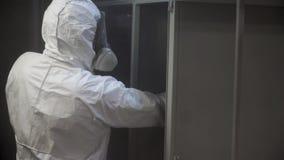 金属零件粉末涂层  夹子 防护套服的一个人喷洒从一杆枪的粉末油漆在金属制品 股票录像