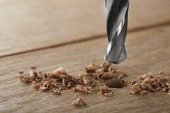 金属钻头做在木橡木板条的孔 免版税库存照片