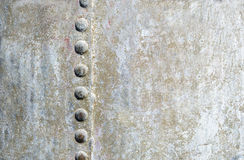 金属水平的背景与铆钉的击倒一边 免版税库存照片