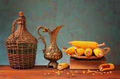 金属水罐、玉米和书 免版税库存图片