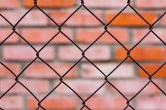 金属滤网篱芭对砖墙 库存图片