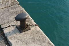 金属系船柱和链子在码头 免版税库存照片