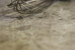 金属wisk特写镜头在使有大理石花纹的厨台,背景机智的 库存图片