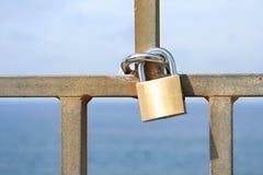 金挂锁有蓝色海背景 免版税库存图片