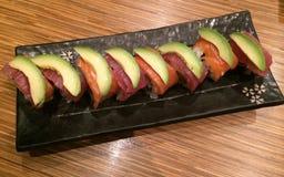 金枪鱼三文鱼和鲕梨寿司卷在餐馆,彩虹寿司卷包括新三文鱼、金枪鱼和鳄梨片,美发师食物 库存图片