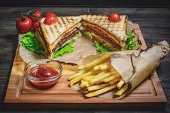 金枪鱼三明治用调味汁和炸薯条在一张木桌上 库存照片