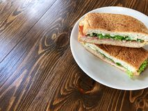 金枪鱼和火腿三明治在白色盘在木桌上 库存图片