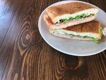 金枪鱼和火腿三明治在白色盘在木桌上 库存照片