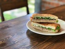 金枪鱼和火腿三明治在白色盘在木桌上 免版税库存图片