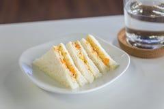 金枪鱼和红萝卜蛋黄酱在板材的全麦三明治吃加上饮用水杯子 库存图片