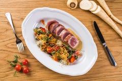 金枪鱼Tagliata与菜意粉的 油煎的金枪鱼与在一块白色板材装饰 开胃菜板材 鱼宴意大利语 图库摄影