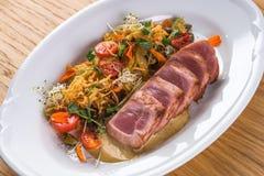 金枪鱼Tagliata与菜意粉的 油煎的金枪鱼与在一块白色板材装饰 开胃菜板材 鱼宴意大利语 免版税库存照片