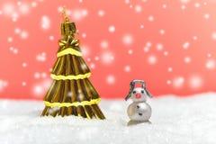 金树装饰品和雪人有多雪的背景 免版税库存照片
