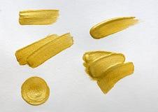 金油漆在白色水彩纸背景升火 免版税图库摄影