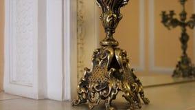 金烛台关闭 金烛台老华美的木碗柜 两葡萄酒金蜡烛台和时钟 免版税库存照片