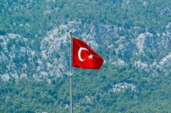 以金牛座山为背景的土耳其旗子 库存图片
