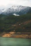 金牛座山和昏暗的岩礁河的绿色倾斜 免版税库存照片