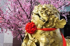 金狮子雕象在一棵装饰的树附近安置了 免版税库存照片