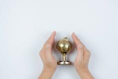 金球奖在手中在白色背景 免版税图库摄影