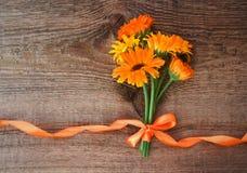 从金盏草花的花束与丝带的在木背景 库存照片