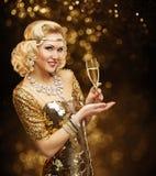 金礼服的妇女喝香宾,美好的减速火箭的时尚的 免版税库存照片
