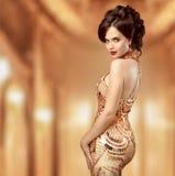 金礼服的美丽的时尚妇女,昂贵的典雅的夫人 库存图片