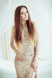 金礼服的美丽的时尚妇女,站立在白色浴附近的典雅的夫人 秀丽构成 发型 深色的女孩夹克皮革 免版税库存图片