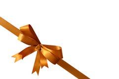 金礼物在白色背景角落对角线隔绝的弓丝带 免版税库存图片